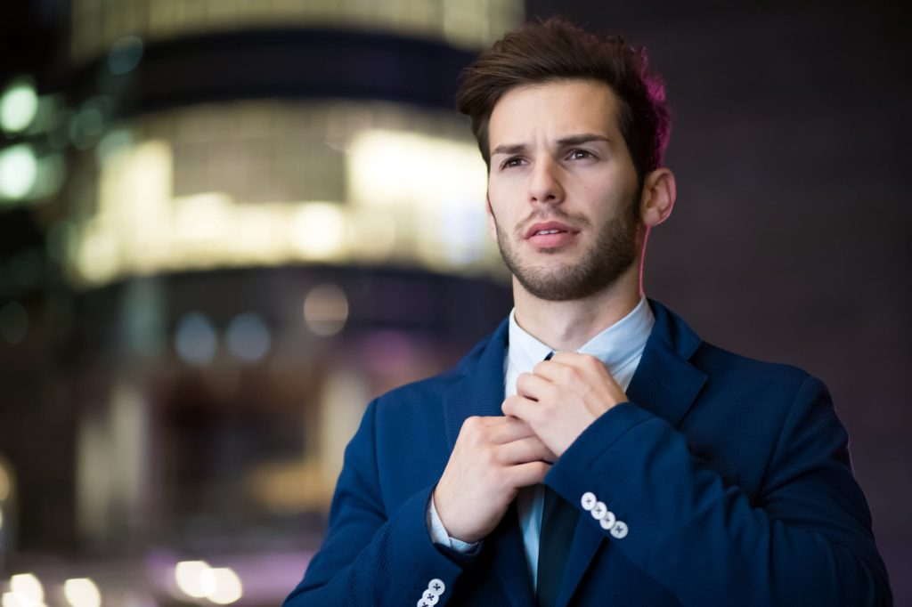 An employee in suit holding his tie